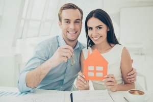 couple holding cut out of house
