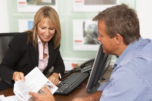 Woman reviewing paperwork with customer