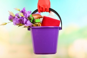bucket with cleaning products and flowers