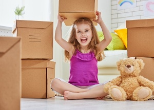 little girl playing with moving boxes