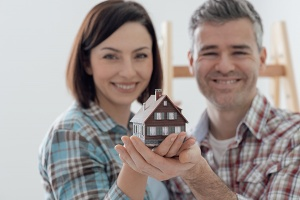 couple holding miniature house model