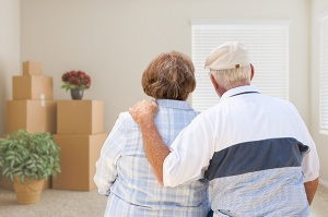 senior couple looking at room with moving boxes